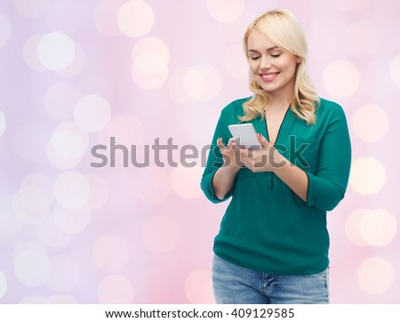 people, technology, communication and leisure concept - happy young woman with smartphone texting message over pink holidays lights background - stock photo