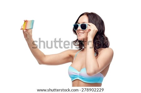 people, technology, summer and beach concept - happy young woman in bikini swimsuit and sunglasses taking selfie with smatphone - stock photo