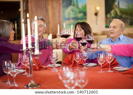People toasting wine glasses at restaurant table