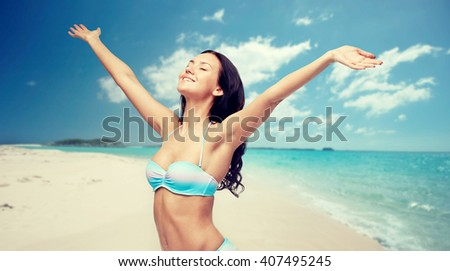 people, tourism, travel and summer concept - happy young woman in bikini swimsuit with raised hands over beach background - stock photo