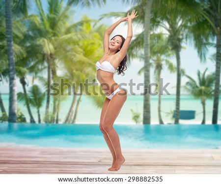 people, travel, swimwear and summer concept - happy young woman posing in white bikini swimsuit dancing with raised hands over tropical beach with palm trees and pool at hotel resort background