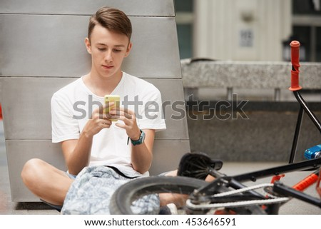People, travel, technology, leisure and lifestyle. Handsome Caucasian teenage boy texting a message on smart phone with serious expression, having rest on the way home, riding his fixed gear bike - stock photo