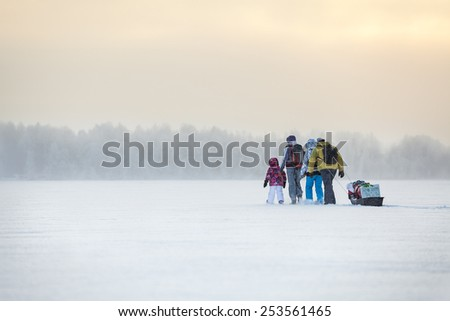 People travel through the blizzard on frozen lake at winter - stock photo