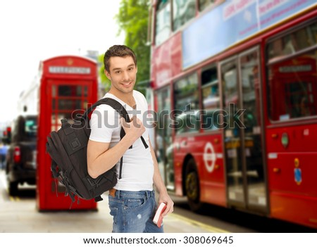 people, travel, tourism and education concept - happy young man with backpack and book over london city bus on street background - stock photo