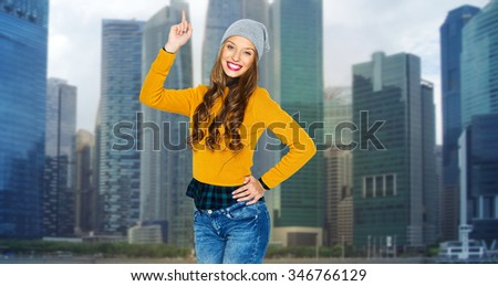 people, travel, tourism and fashion concept - happy young woman or teen girl in casual clothes and hipster hat pointing finger up over city buildings background - stock photo