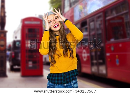 people, travel, tourism and fashion concept - happy young woman or teen girl in casual clothes and hipster hat having fun over london city street background - stock photo