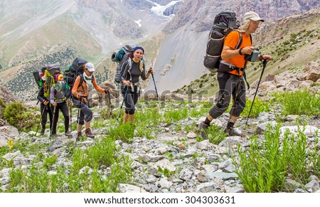People traveling in mountains. Large group of tourists of different sex ethnic nation race age young and old man woman walking up on rocky path with green grass forest and mountain peaks around - stock photo