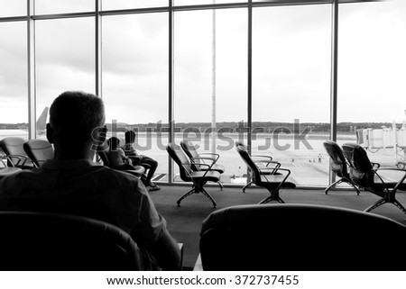 People traveling on airport; waiting at the plane boarding gates. - stock photo