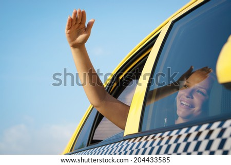 people travelling. Female passenger in taxi with arm outside of car window waving hand. Concept of freedom - stock photo