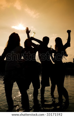 People (two couples) on the beach dancing to music, drinking and having a lot of fun in the sunset - only silhouette of people to be seen - stock photo