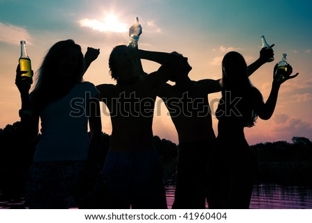 People (two couples) on the beach dancing to music, drinking and having a lot of fun in the sunset (only silhouette of people to be seen, people having bottles in their hands) - stock photo