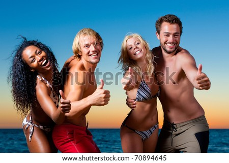 People (two couples) on the beach having a party and having a lot of fun in the sunset - stock photo