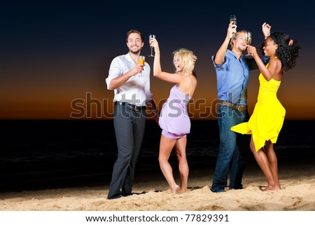 People (two couples) on the beach having a party and lots of fun in the sunset, they are wearing smart casual clothes and dance - stock photo