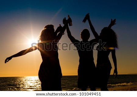 People (two couples) on the beach having a party, drinking and having a lot of fun in the sunset (only silhouette of seen, people having bottles in their hands with the sun shining through)