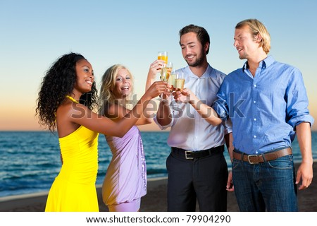 People (two couples) on the beach having a party, drinking and having a lot of fun in the sunset, they are wearing smart casual clothes and drink champagne - stock photo