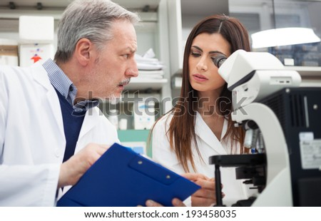 People using a microscope in a chemical laboratory - stock photo