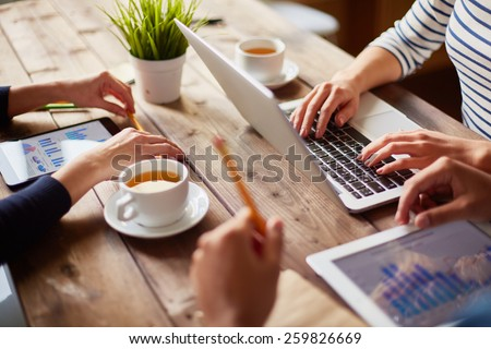 People using different devices at one table - stock photo