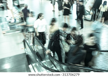 People using escalator - moving blur - stock photo