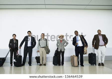 People waiting at airport with luggage - stock photo