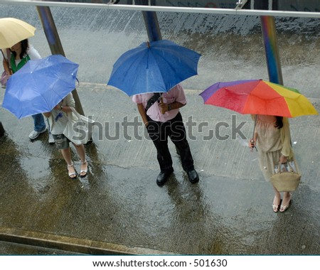 people waiting at busstop in the rain - stock photo