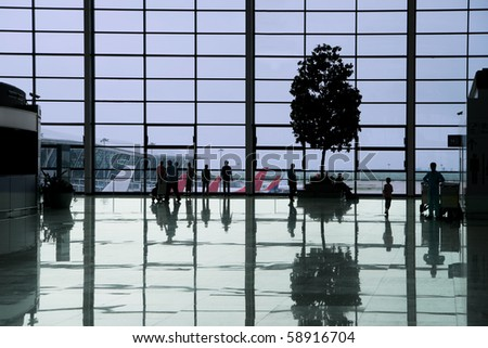 People waiting in the departure hall of a modern airport - stock photo