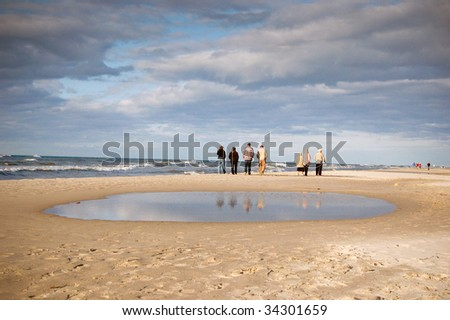 People waking along the seashore
