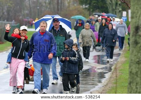 People walk in the rain for a fund-raising walkathon for multiple sclerosis. Editorial use only. - stock photo