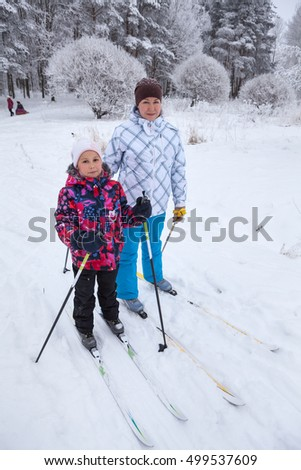 People walk on ski in winter forest, Caucasian woman with girl skiing together