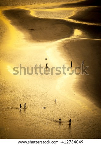 people walk on the beach of Chao Laow in Chanthaburi province in thailand with beautiful golden sunlight on the sea - stock photo