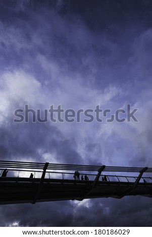People walking across London's Millennium Bridge, silhouetted against a dark, stormy sky. - stock photo