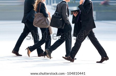 People walking against the light background of an urban landscape. - stock photo