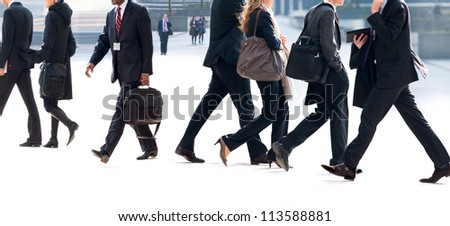 People walking against the light background of an urban landscape.