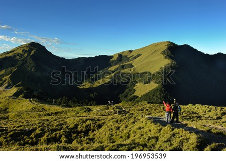 People walking along a path toward some lush green hills. - stock photo