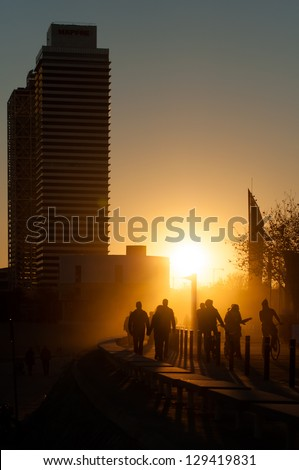 People walking at Port Olimpic in Barcelona at sunset. Catalonia, Spain. - stock photo