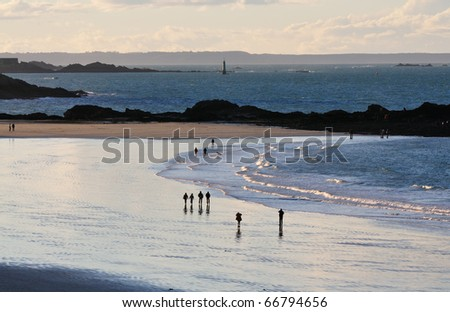 People walking at the beach of Saint-Malo at sunset.