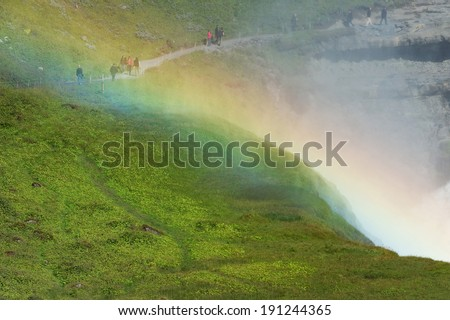 People walking behind the rainbow, Gullfoss (golden falls) waterfall, Golden circle, Iceland - stock photo