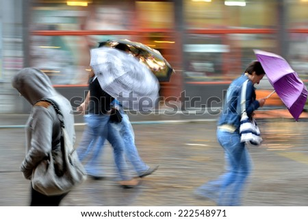 People walking down the street on rainy day. Intentional motion blur - stock photo