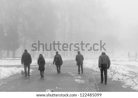 people walking in foggy winter landscape with snow - stock photo