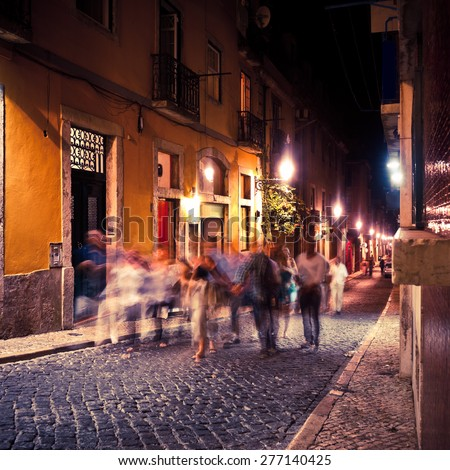People walking in Lisbon at night - stock photo