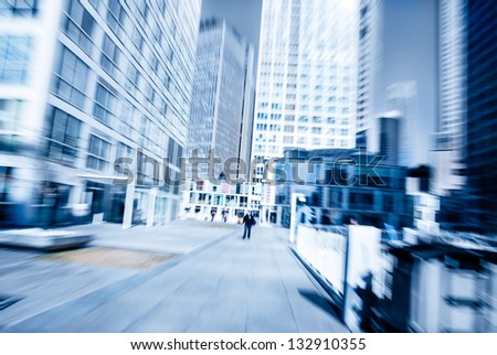 People walking in the business district, with skyscrapers. - stock photo