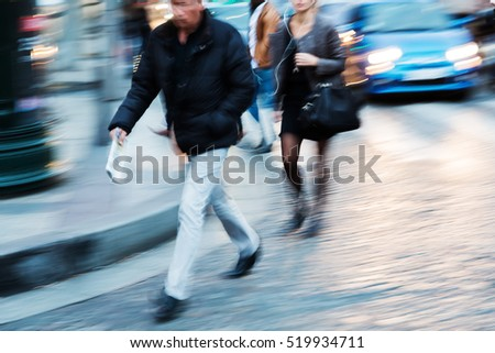 people walking in the city at dusk with intentional motion blur