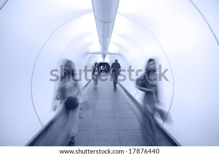 people walking in tunnel in blue tone - stock photo