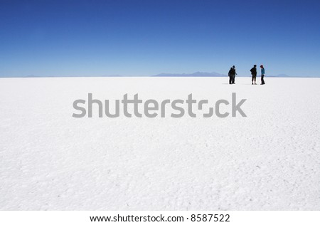 people walking in very white uyuni salt lake in bolivia to relax - stock photo