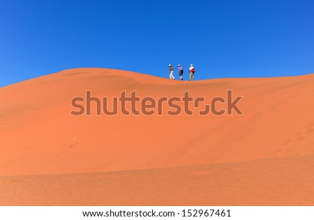 People walking on beautiful dune of Namib desert, traveling and hiking in South Africa  - stock photo