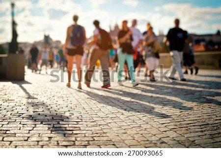 People walking on the Charles Bridge in Prague during a sunny summer day