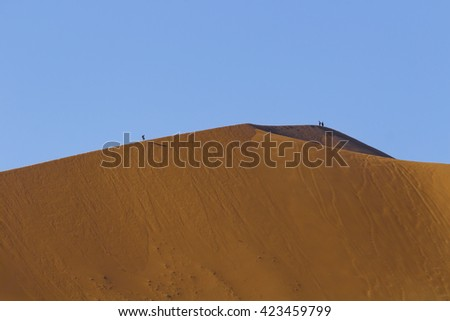 People walking on the crest of a red dune in the Namib Desert, in Sossusvlei, in the Namib-Naukluft National Park of Namibia