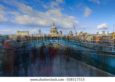 People walking over Millennium bridge in London, England UK. St Pauls cathedral in the background.