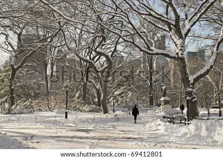 People walking through Central Park in New York after a fresh snowfall. - stock photo