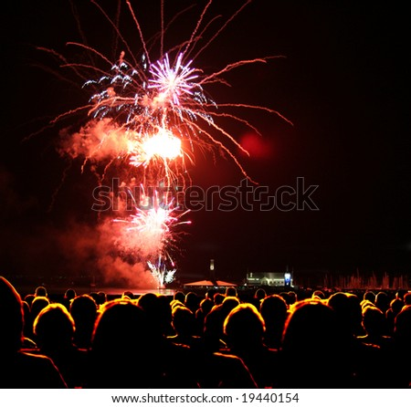 People watch fireworks display - stock photo