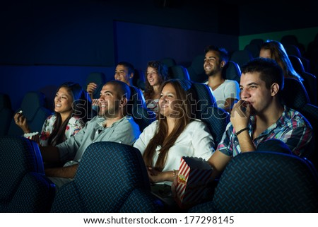 People watching movie in cinema. Selected focus on boy in the first row on the right side - stock photo